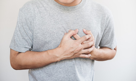 a man touching his heart. Heart attack, and others heart disease concept, on white background Standard-Bild