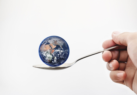 Blue planet earth on spoon, isolated on white background.