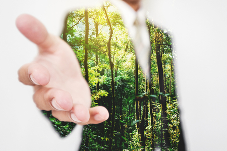 Double exposure, Businessman stretching hand to hand shake with Green trees in the forest. Eco friendly and sustainable business Stock Photo