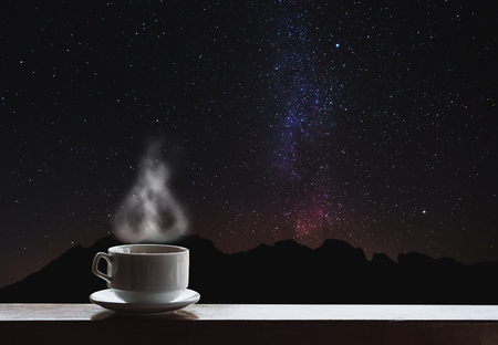 Cup of hot drinks on the table with beautiful Milky Way with silhouette mountain ride. Milky Way sightseeing at night