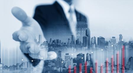 Doppelbelichtung Geschäftsmann Verlängerung Hand mit Gebäuden in der Stadt und zeigt Graph Standard-Bild