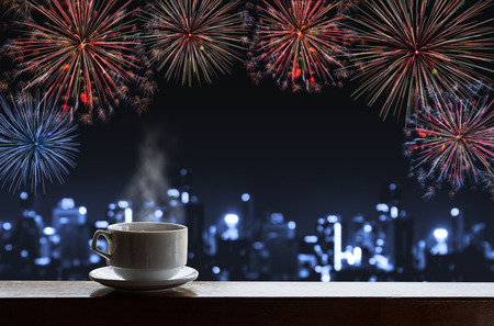 Cup of hot drinks on wooden desk with new year celebrate fireworks on night sky