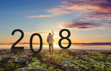 Freedom man standing on the rock, raising hand up under sunset. 2018 New Year celebrating Stock Photo