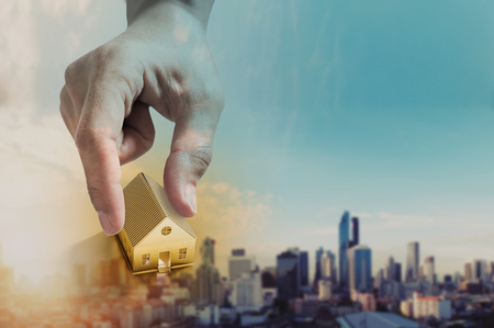 Hand holding golden house, real estate investment and buying house concept, defocus city in sunrise background