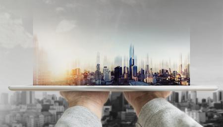 Hand holding digital tablet with futuristic modern buildings hologram on screen Standard-Bild
