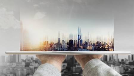Hand holding digital tablet with futuristic modern buildings hologram on screen Foto de archivo