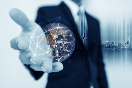 Businessman holding globe hologram with network connection lines. Global business networking, currency exchange and travel around the world concept.