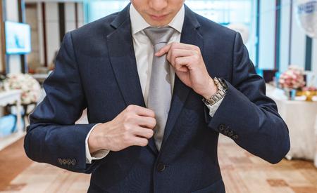 Young man in formal blue suit tying necktie