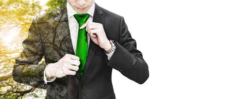 Doppelbelichtungsgeschäftsmann, der grüne Krawatte und großen Baum mit Sonnenlicht, auf weißem Hintergrund mit Kopienraum bindet Standard-Bild