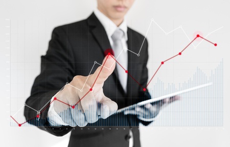 Businessman using digital tablet and pointing finger on graph diagram. Break even point, business growth, investment and finance concept
