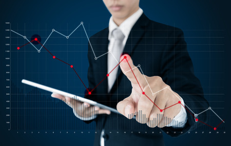 Businessman using digital tablet and pointing finger on falling graph diagram. Business finance and economy crisis