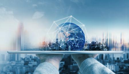 Mano que sostiene la tableta digital con tecnología de conexión de red global y edificios modernos.