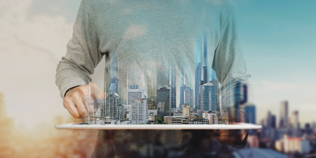 ein Mann mit digitalem Tablet und modernem Gebäudehologramm. Immobiliengeschäft und Gebäudetechnikkonzept