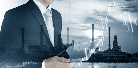 Investment in energy and fuel business. Double exposure Businessman working on digital tablet with power plant, oil refinery and raising graph background