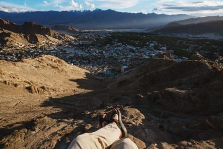 Travelling in Leh city, in Ladakh, India. a man sitting on cliff enjoying leh city view in the morning