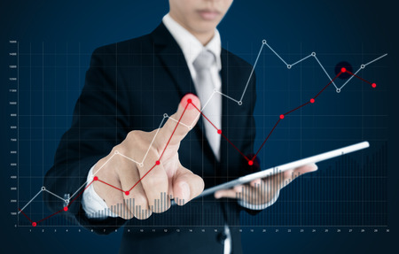 Businessman pointing raising graph on screen. Business growth, investment and finance concept