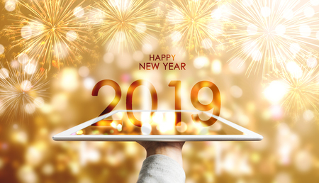 Happy New Year 2019, Hand holding digital tablet with luxury gold Bokeh fireworks background 免版税图像
