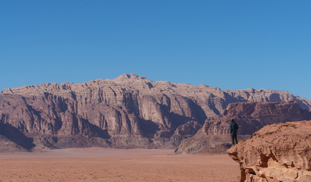 Traveler standing on edge of mountain cliff, at Wadi Rum desert in Jordan. Travel lifestyle and adventure and journey Imagens