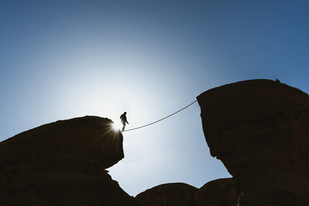 a man balancing walking on rope over precipice. Business, risk taking, challenge,bravery, and concentration