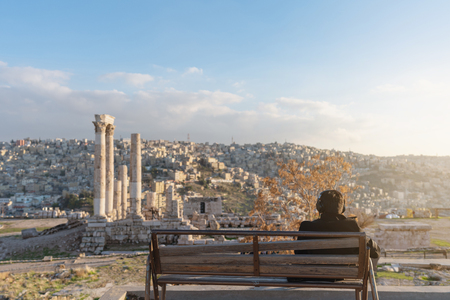 a man sitting alone listening music by headphone in spring at Citadel in Amman, Jordan