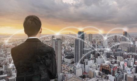 Netzwerktechnologie, Logistik und Blockchain-Geschäft. Geschäftsmann, Blick auf die Stadt bei Sonnenuntergang