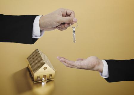 eal estate business, residential rental and investment. Businessman handover house key Standard-Bild