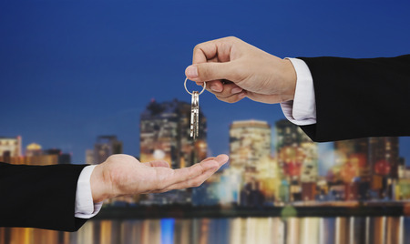 Real estate business, residential rental and investment. Businessman handover keys, with city at night backgrounds 版權商用圖片