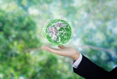 Business globale verde e ambientale. Globo della tenuta della mano dell'uomo d'affari con il fondo verde del bokeh. Archivio Fotografico
