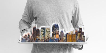 Negocio inmobiliario, tecnología de la construcción y ciudad inteligente. un hombre que usa tableta digital con holograma de edificios