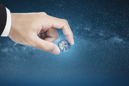 Businessman picking the world, on blue starry space background.