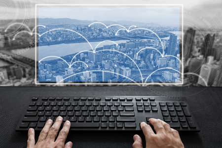 Hand typing on computer keyboard with futuristic screen and city background