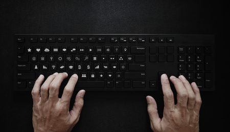 Hand typing on computer keyboard, with application icons on button. Application Programming Interface Imagens