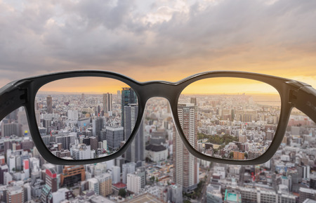 Looking through eyeglasses to city sunset view, focused on lens with blurry background Stock Photo