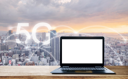 Internet networking, 5G and wireless technology. Computer laptop with blank white screen, on wooden desk and city view in sunset with 5G internet networking