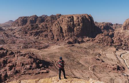 Traveler standing on cliff enjoying desert sightseeing in Petra, Jordan