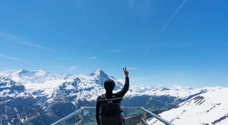 a man with backpack raising hand up with Swiss Alpine mountains view in Grindelwald, Switzerland Imagens