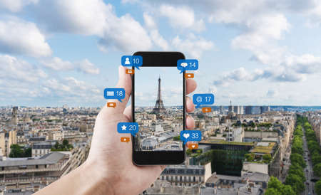Hand using mobile smart phone taking photo of Eiffel tower in Paris, France with social media and social network notification icons