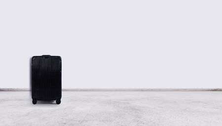 Black travel baggage , on white wall and floor