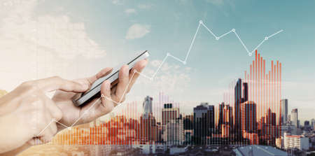 Hand holding mobile smart phone with raising financial graphs, on city background