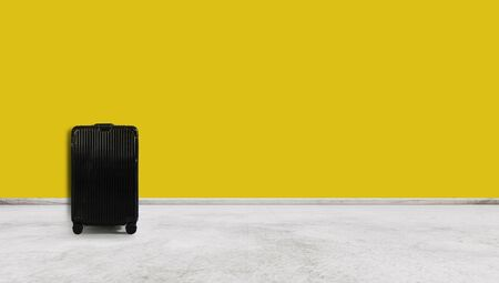 Black travel baggage , on yellow wall and white floor 版權商用圖片