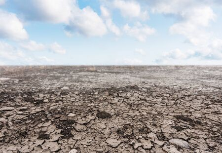 Dry cracked drought ground with blue sky and white clouds