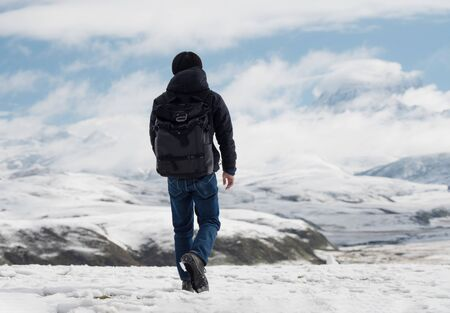 a man with backpack walking on snow, trekking in winter