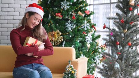 Young Asian girl embracing gift box with happy face in Christmas morning