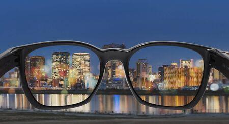 Regardant à travers des lunettes vers la ville la nuit, concentré sur l'objectif avec un arrière-plan flou