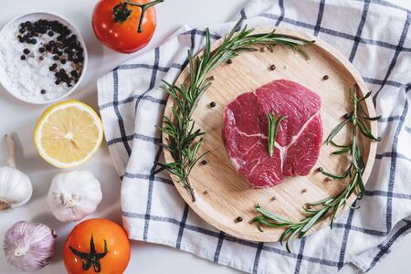 Raw beef steak Tenderloin fillet, with tomatoes, Rosemary and lemon, on wooden board