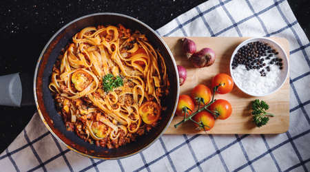 Pasta Bolognese tomatoes sauce in frying pan with fresh ingredient on wooden tray
