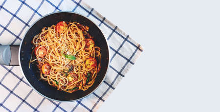 Pasta Bolognese tomatoes sauce in frying pan, on tablecloth, and white background