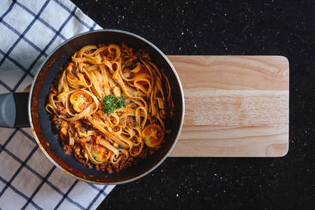 Pasta Bolognese tomatoes sauce in frying pan, on wooden plate