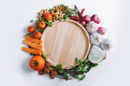 Healthy Eating. Wooden dish surrounding with fresh healthy vegetables, on white background Imagens