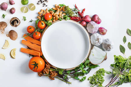 Healthy Eating. White ceramic dish surrounding with fresh healthy vegetables, on white background